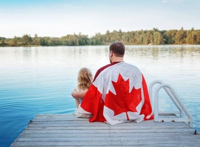 Father and Daughter Wrapped in Large Canadian Flag